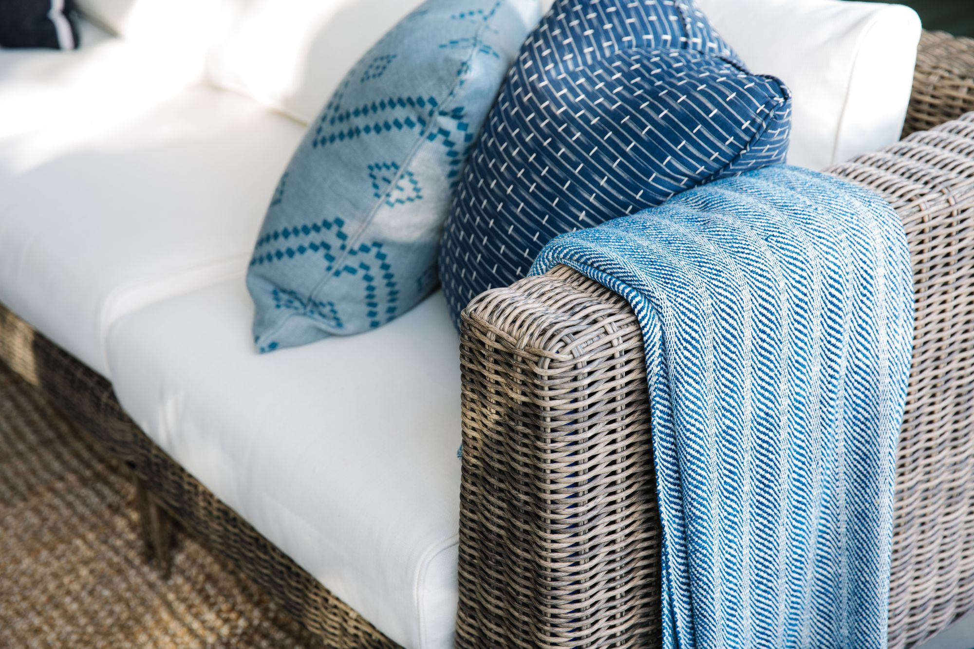 Pillows and throw blanket on patio furniture