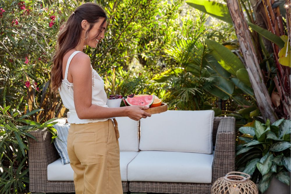 Woman serving up summer snacks near her outdoor sofa