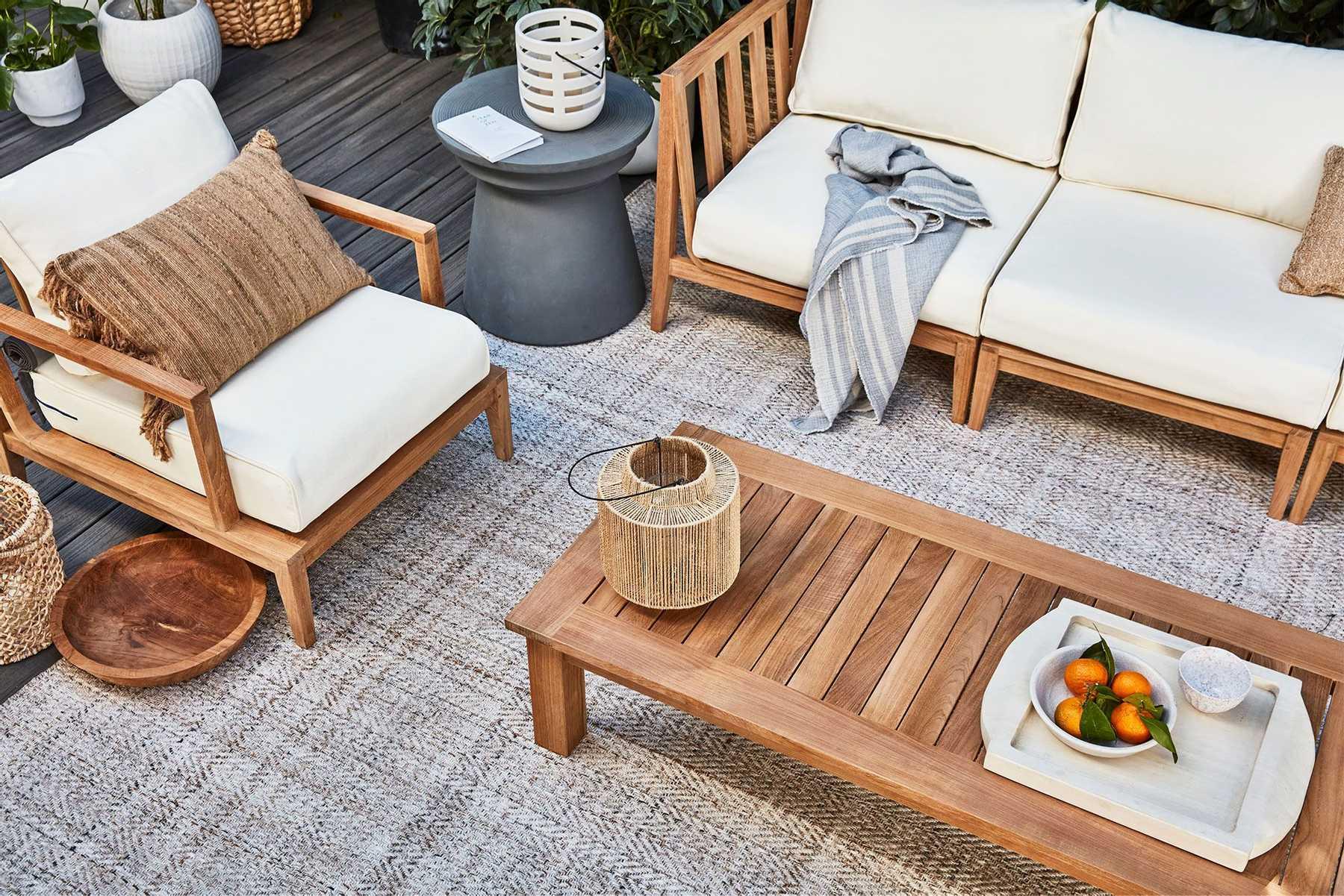 Light wood outdoor sofa with cream cushions