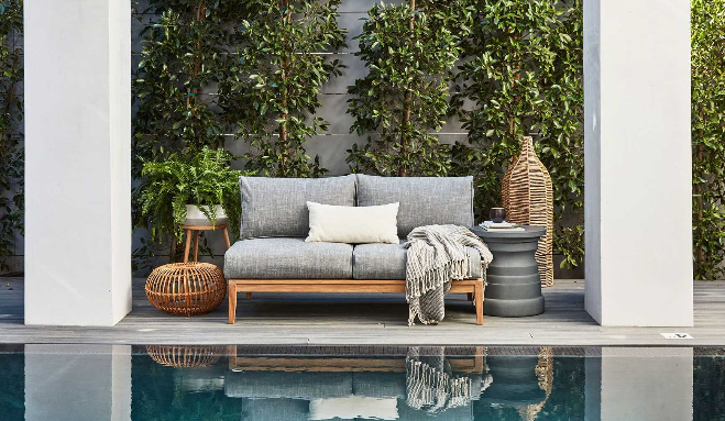Teak outdoor furniture with grey cushions by the pool