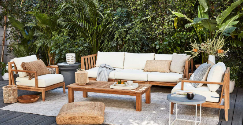 teak outdoor furniture with white cushions in front of a wall of plants