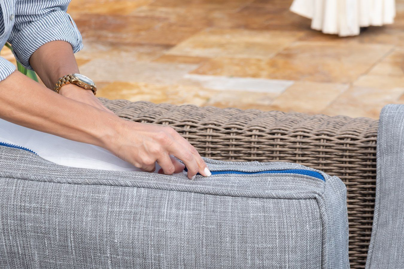 Woman putting stuffing back in fabric for cushion of patio furniture