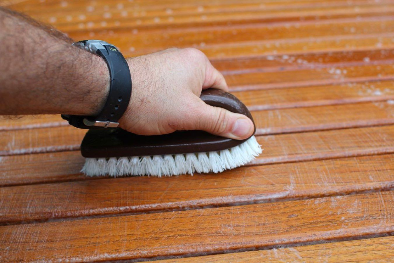 Man scrubbing teak wood after learning how to clean patio furniture