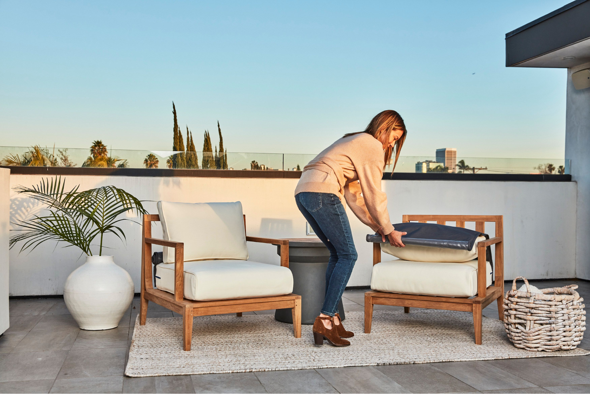 Woman setting up cushions on patio furniture