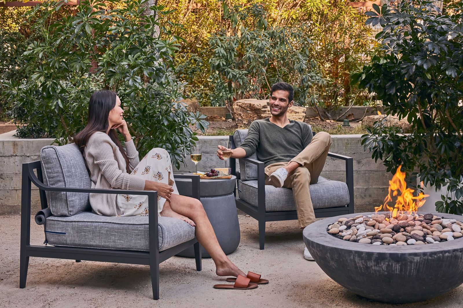 Couple drinking wine while sitting on aluminum outdoor furniture