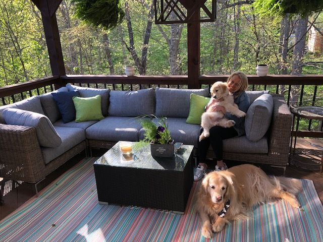 Woman enjoying her outdoor furniture with her two dogs