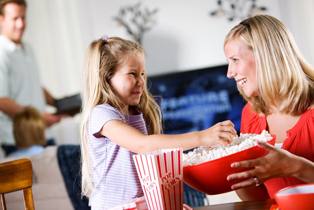 Mom and daughter eating popcorn during a backyard movie night