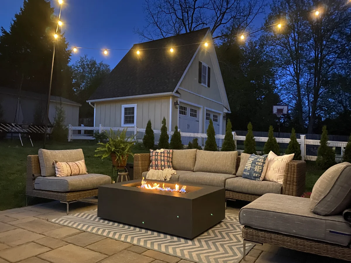 Outdoor patio furniture at night lit up by lights and a fire