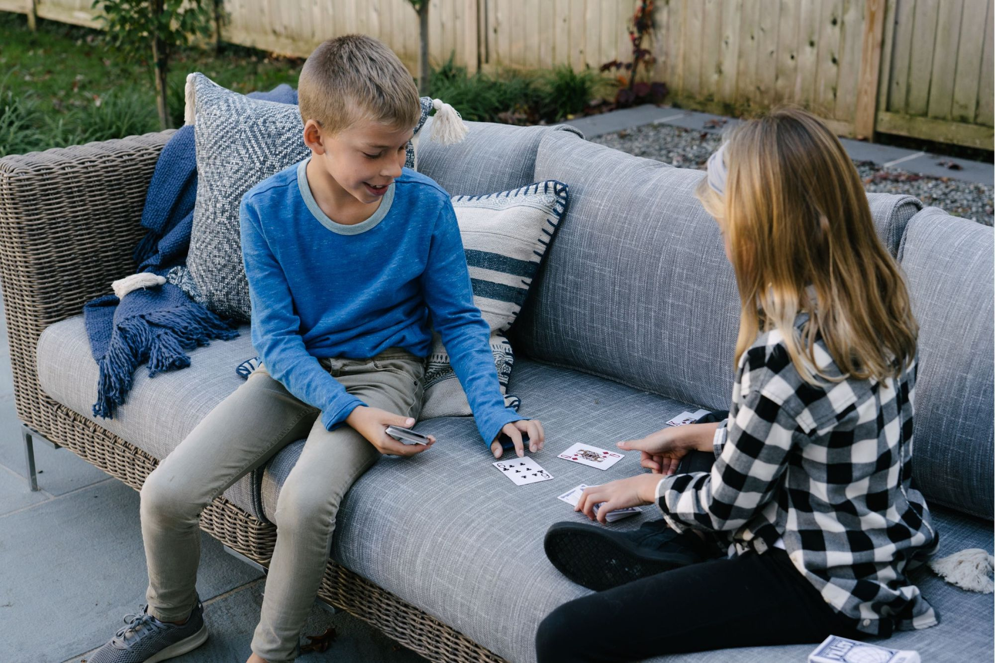 Two kids playing cards on outdoor furniture