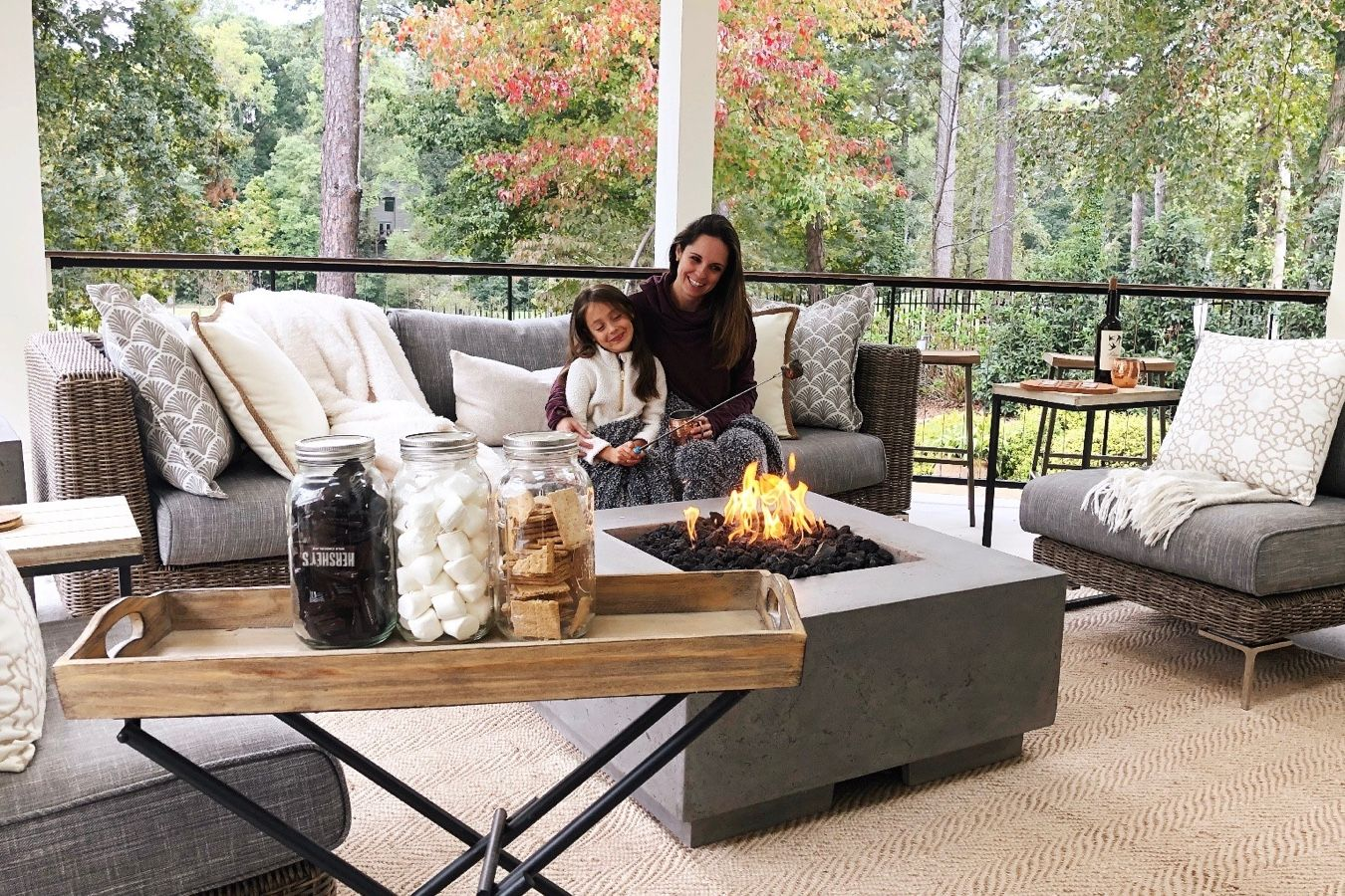 Mom and daughter making s'mores in their backyard firpit
