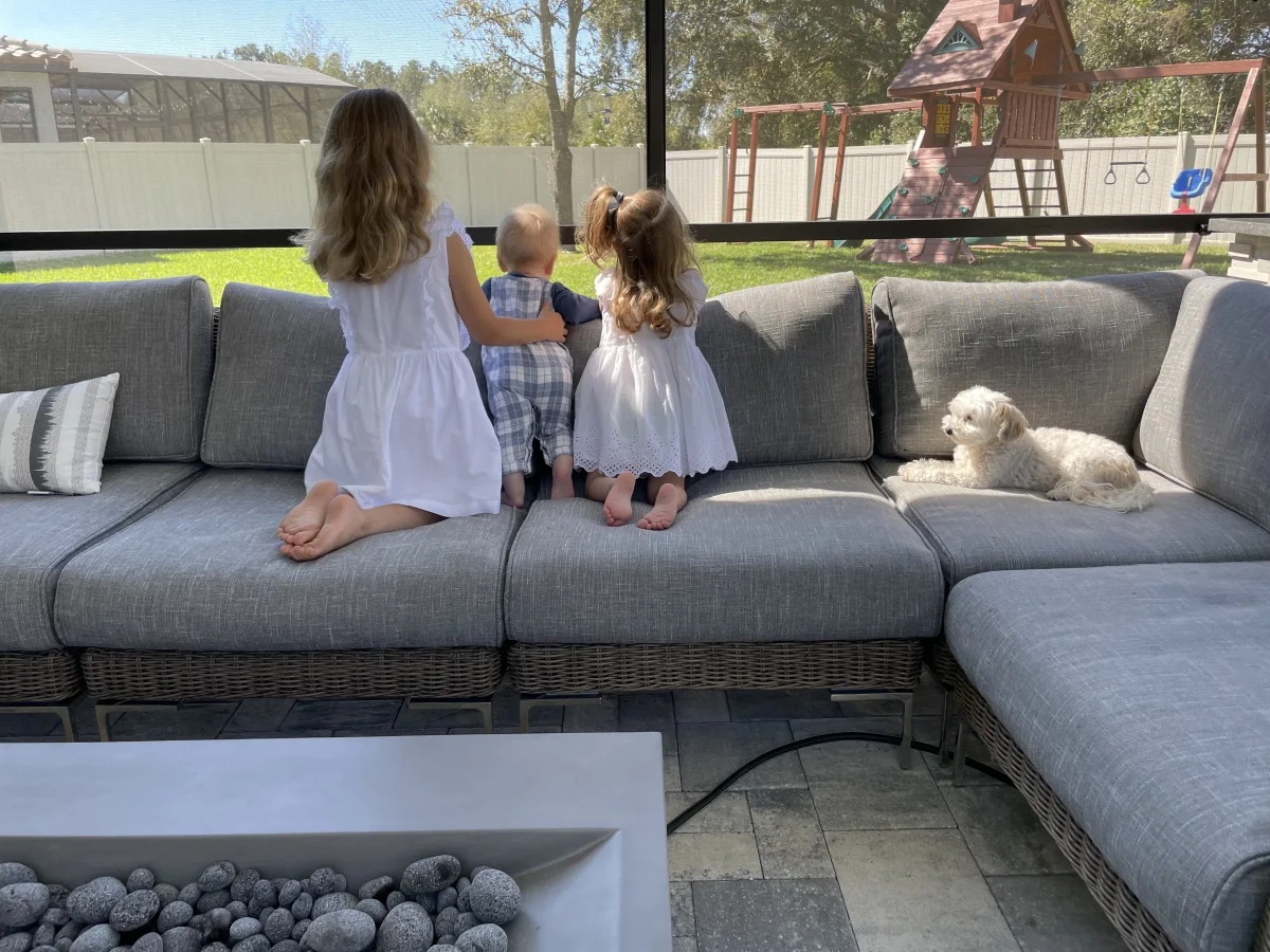 Three kids looking out patio with screen.