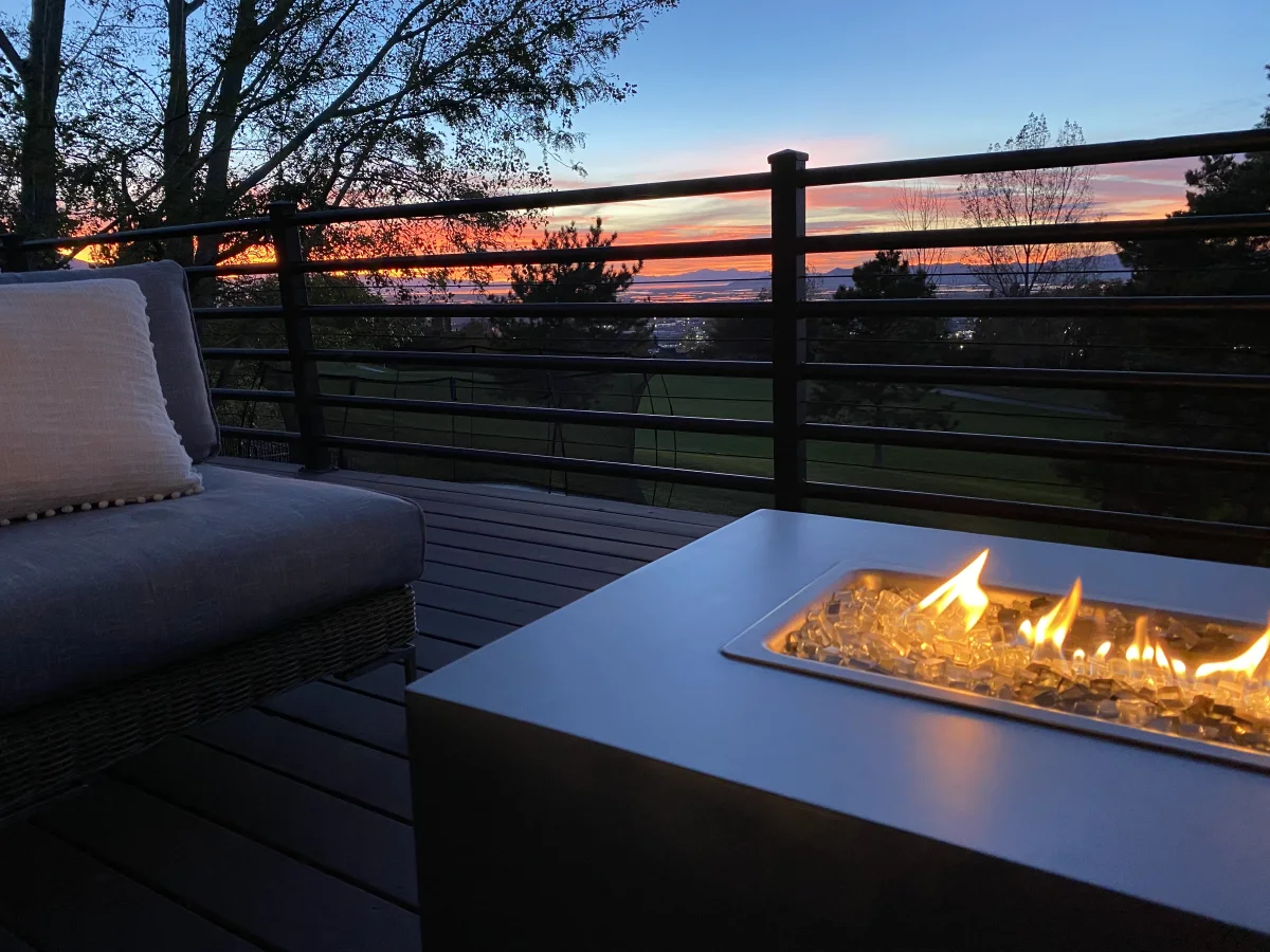 Deck with glass fire pit over looking grass and beautiful sunset