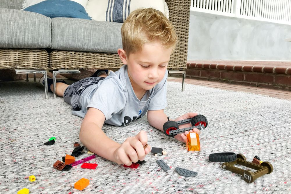 Kid playing with legos on an outdoor rug