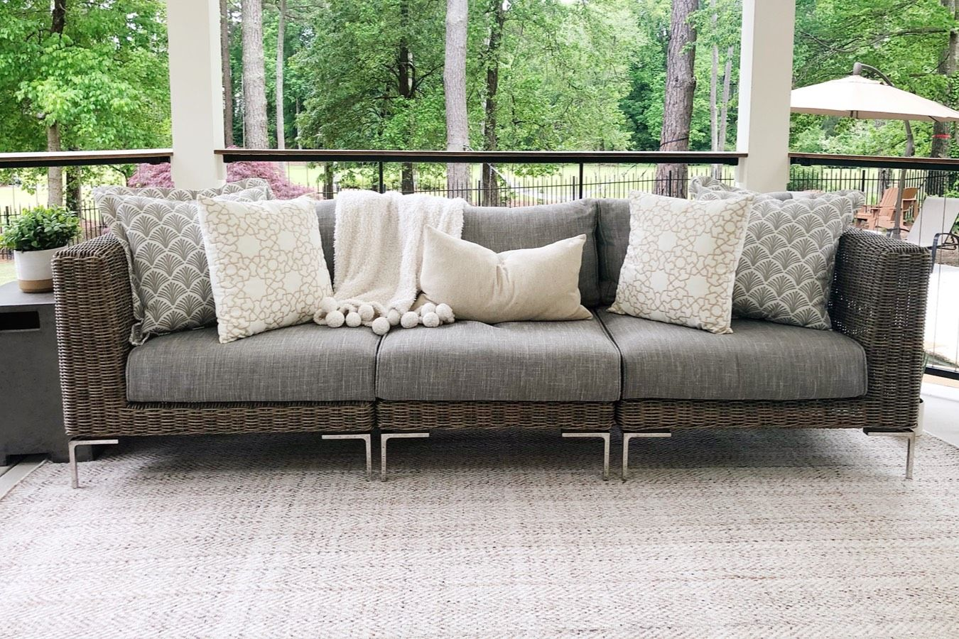 Wicker outdoor furniture with grey and cream colored cushions and pillows