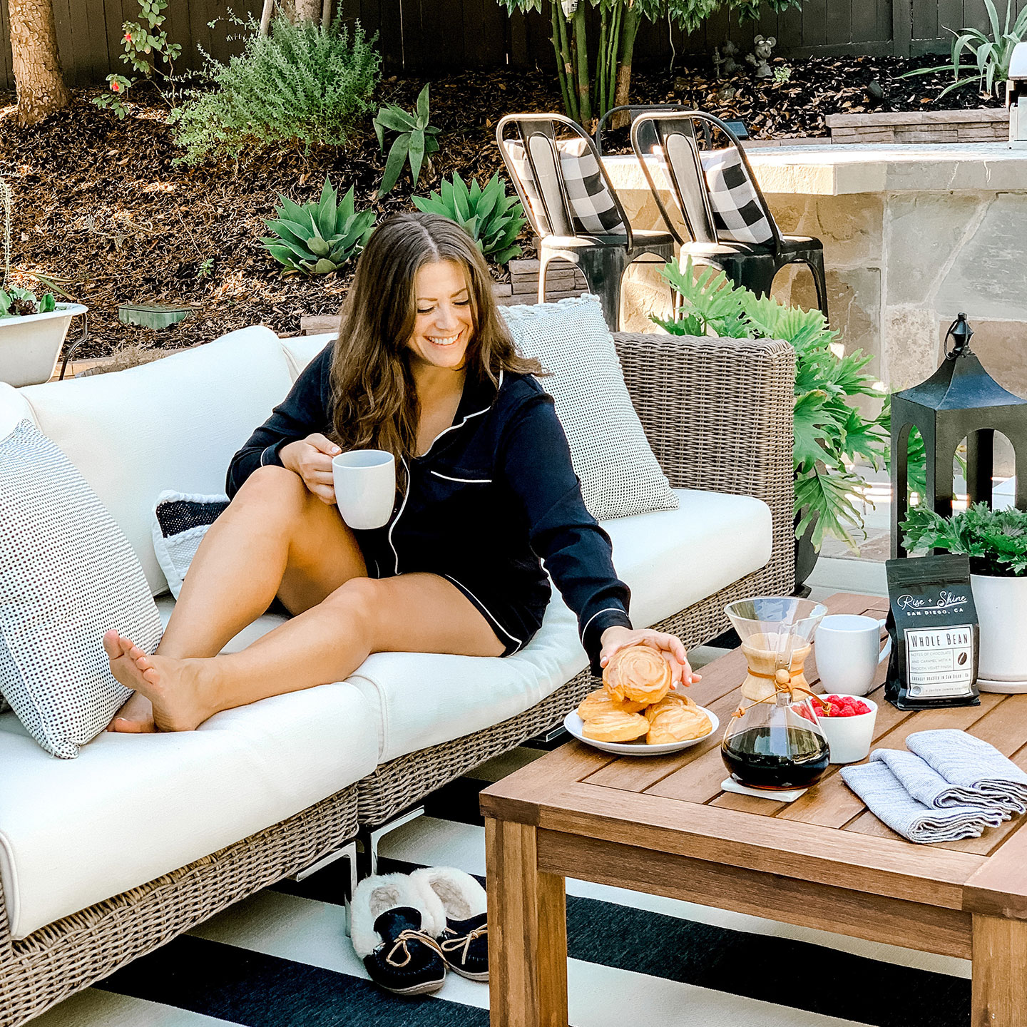 Woman enjoying breakfast and coffee out on her garden furniture