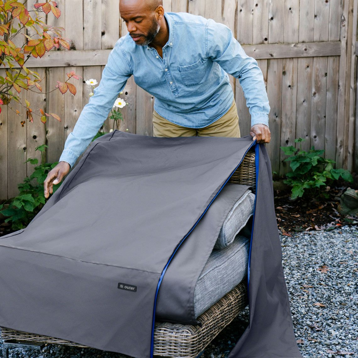 Man putting outdoor furniture covers on