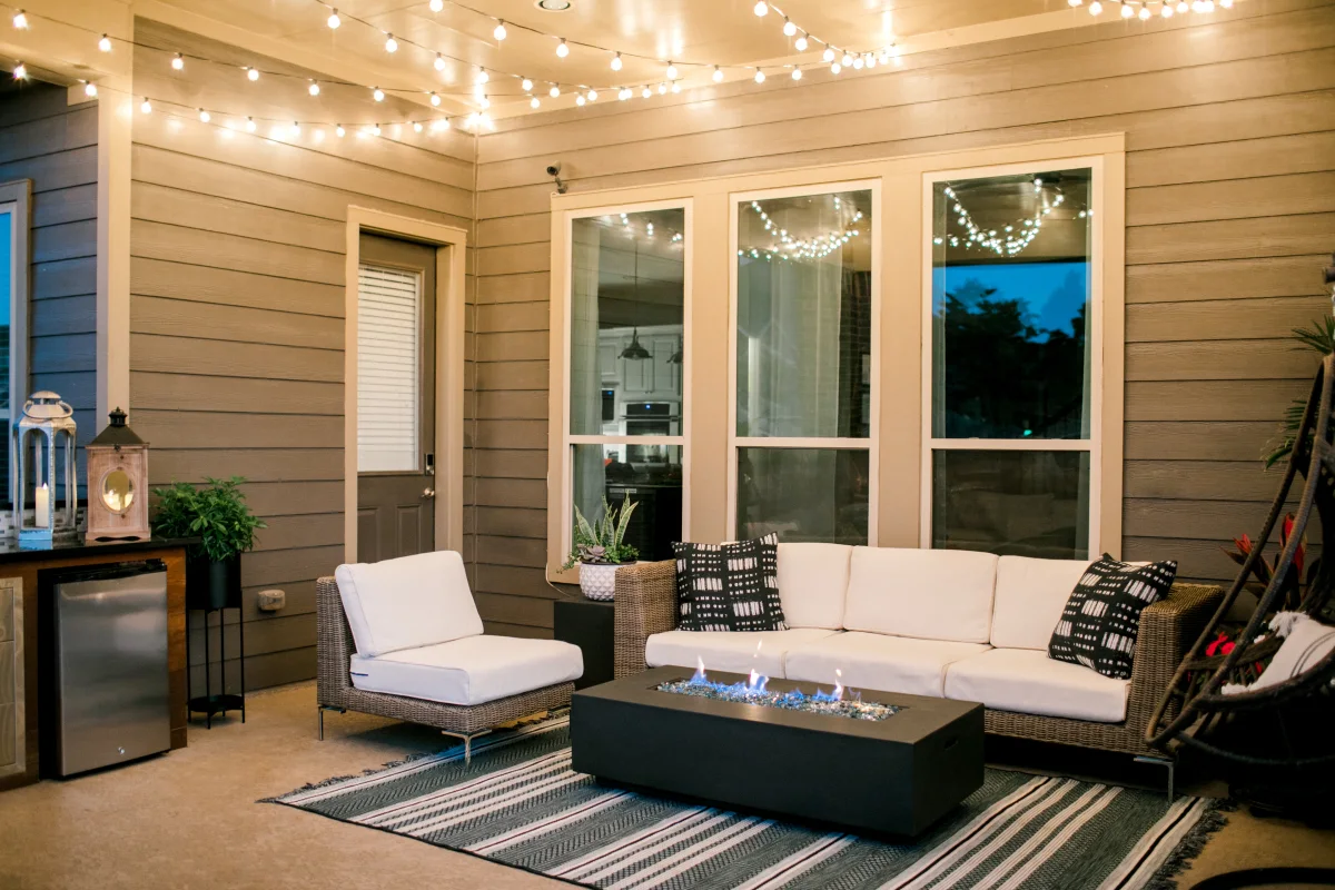 outdoor wicker furniture set up at night lit up by string lights and a glass fire pit table