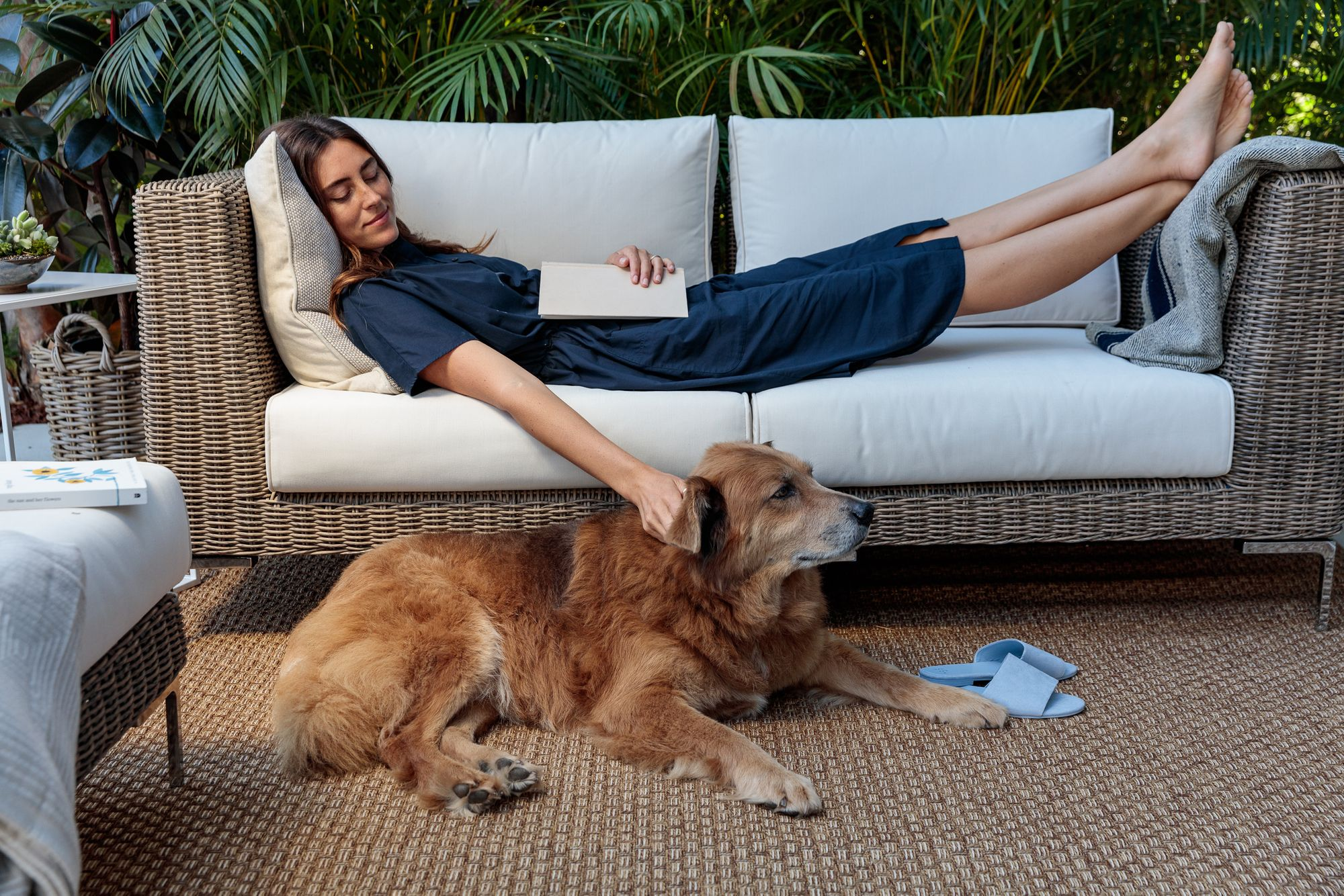 Woman laying on outdoor wicker furniture while petting her dog