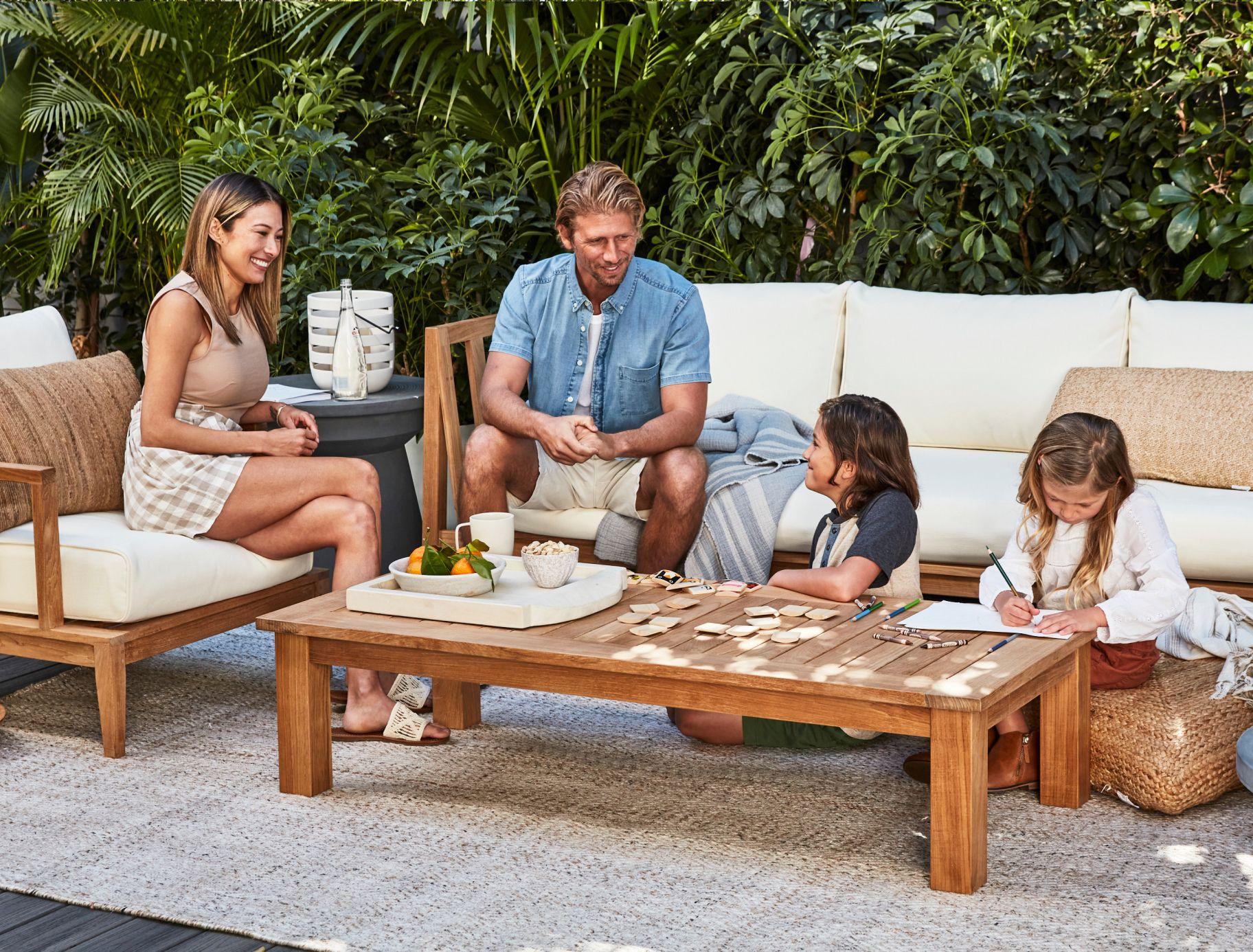 Family outside enjoying their teak wood furniture