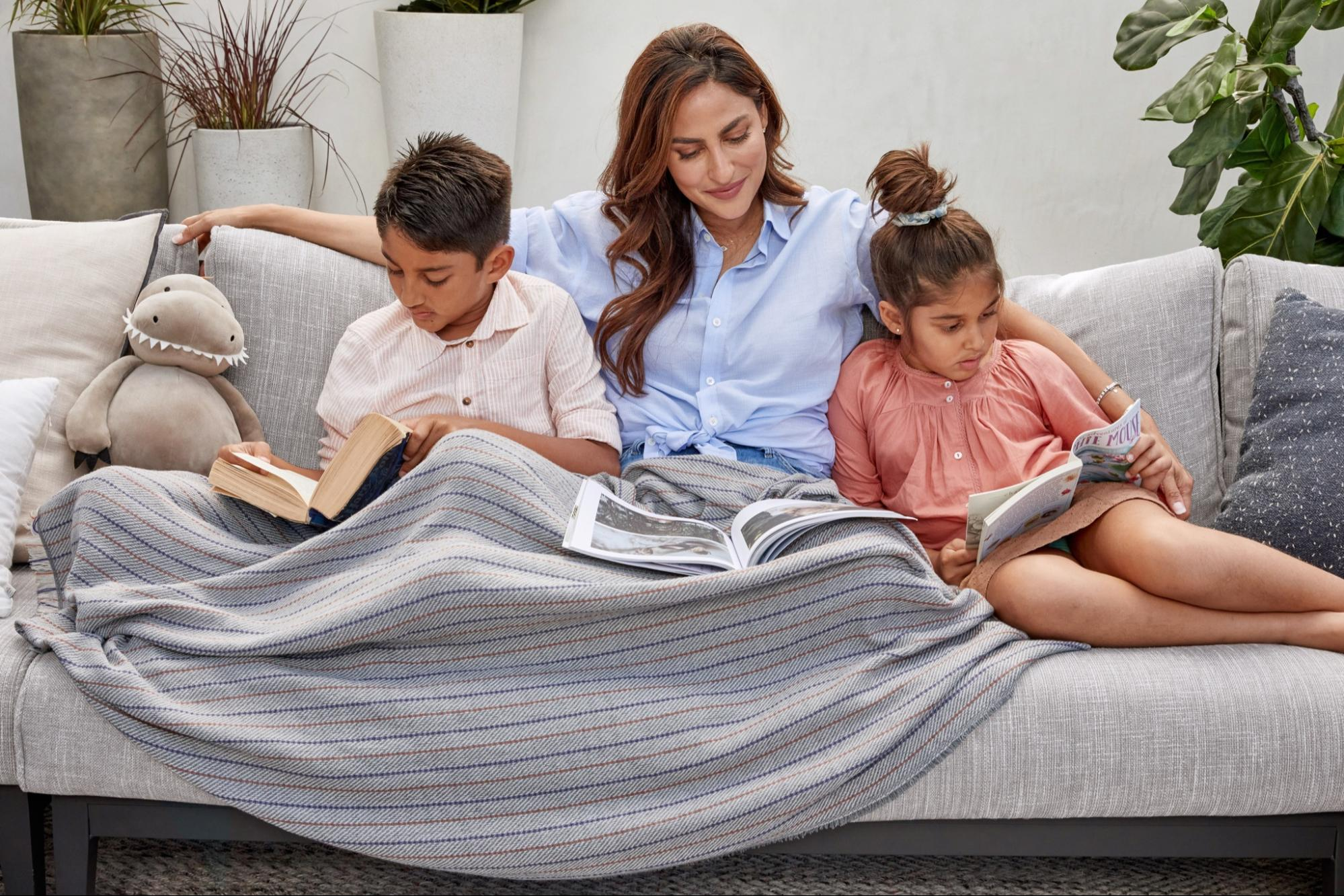 Family using a throw blanket to help keep mosquitos from biting
