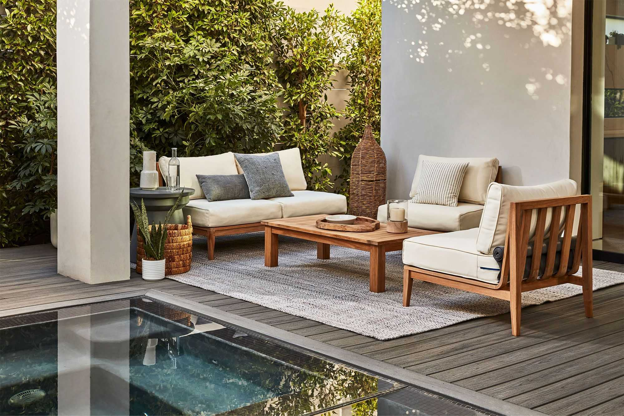 patio table with chairs and white cushions near a pool