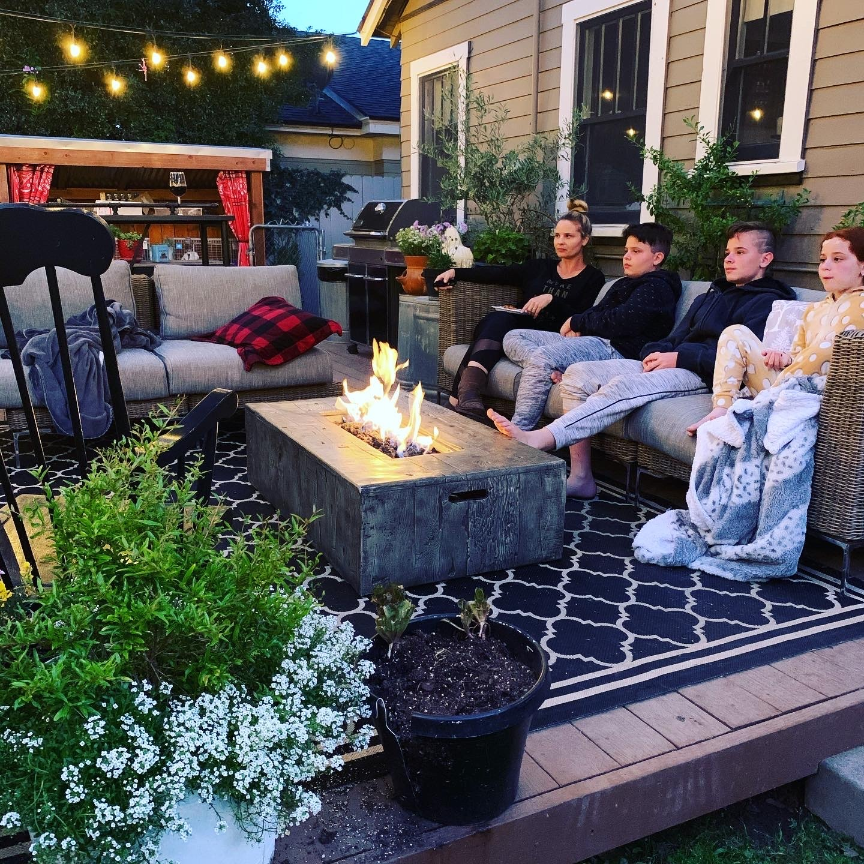 Family watching a movie while having a backyard bonfire