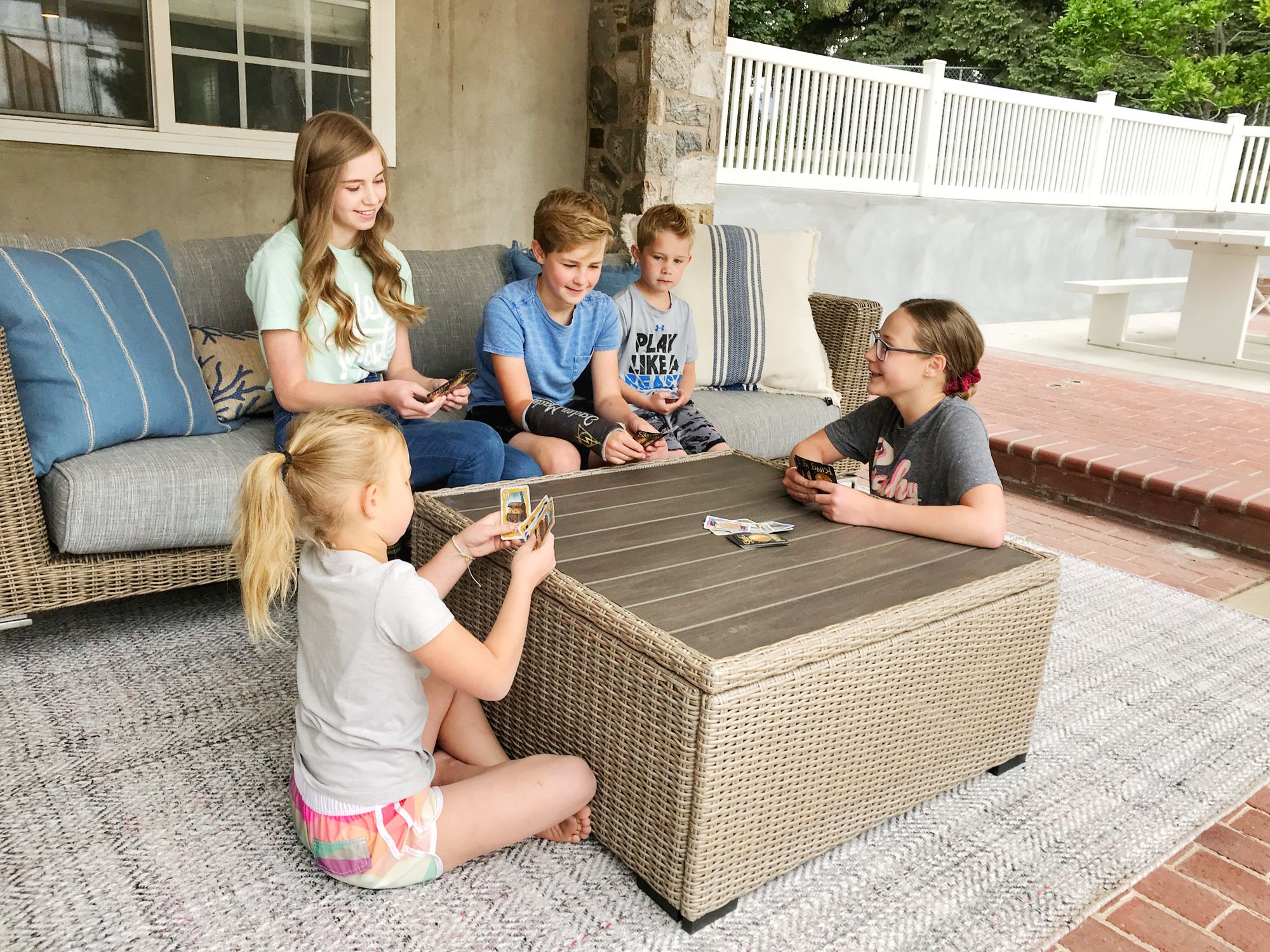 Family playing cards on outdoor rug