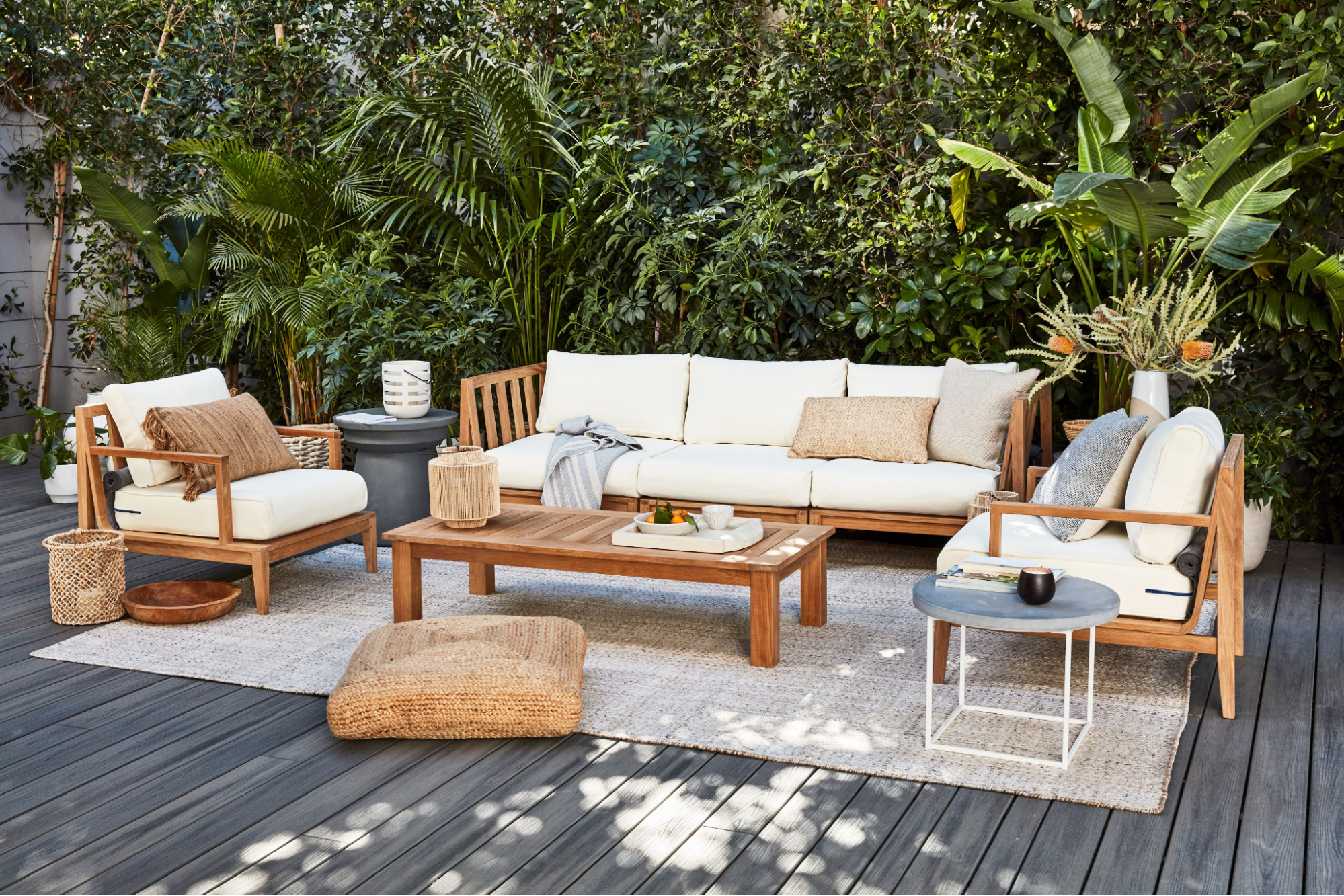 Teak outdoor furniture on a large outdoor rug