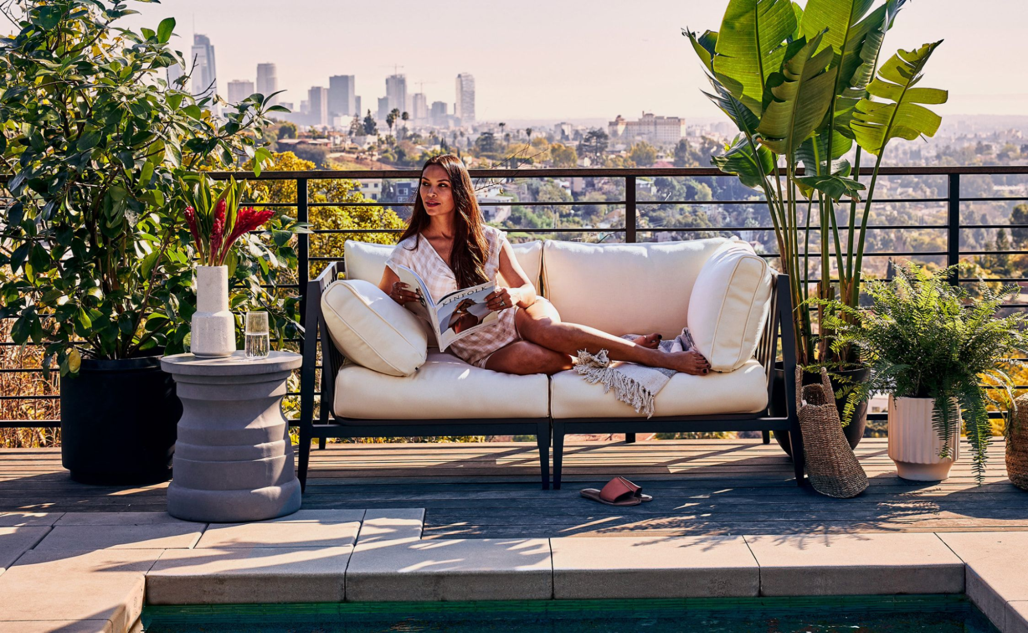 Woman sitting on a loveseat on a rooftop patio near a pool