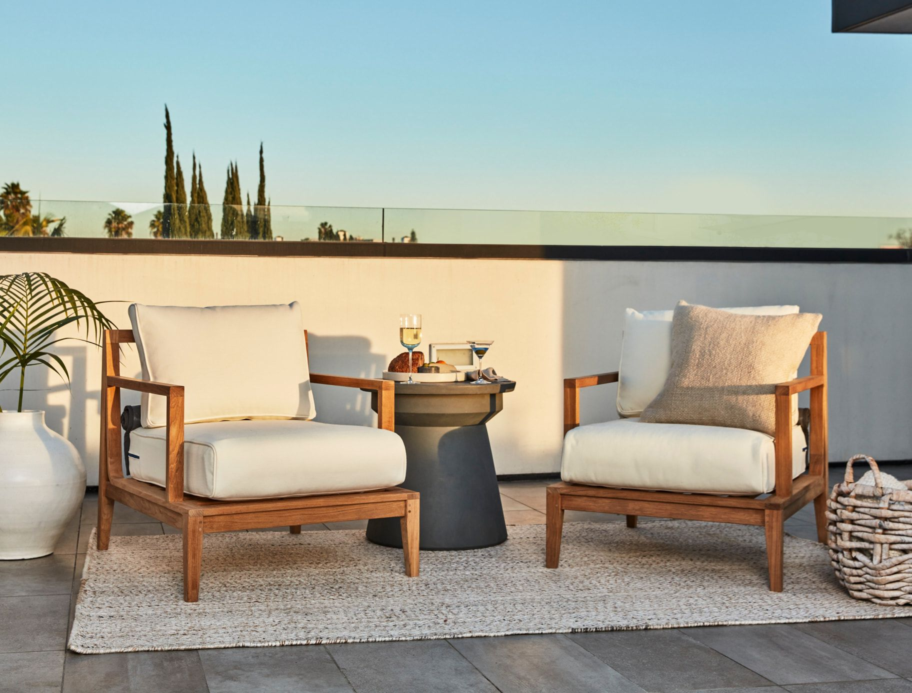 Two teak outdoor chairs with white cushions